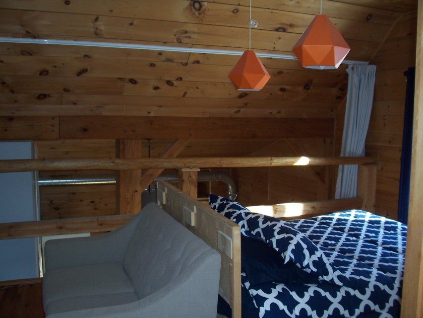 The loft area, with the queen bed and love seat...