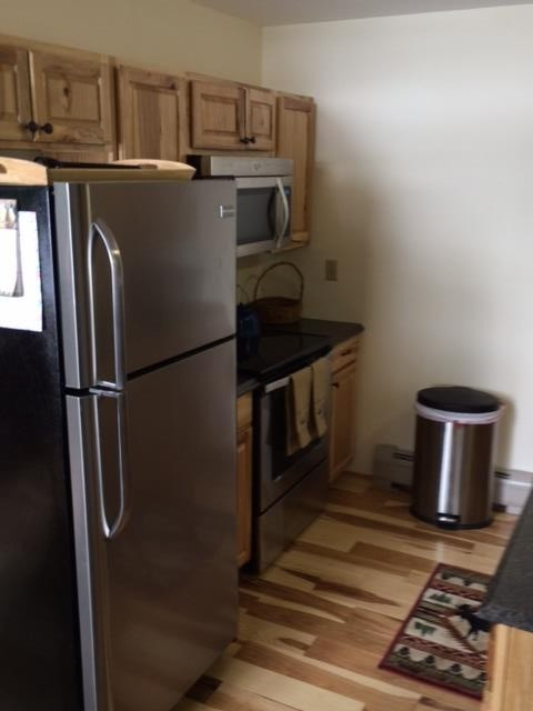 Kitchen with refrigerator, oven and microwave