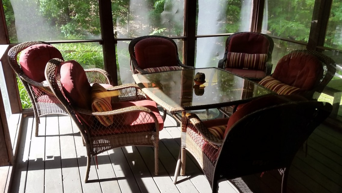 Screed porch has table & comfy wicker chairs