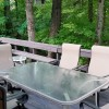 Deck w/ table, gas grill is surrounded by trees & birds