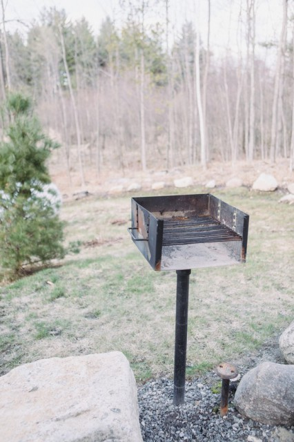 Outdoor grill for cooking!  A bench is nearby