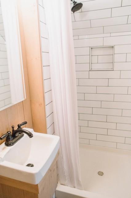 Shower has a shelf for storage.