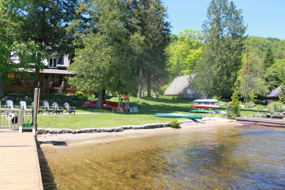 View from lake with chairs, kayaks & canoes for you!