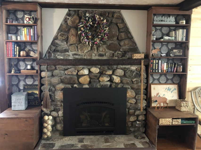 Fieldstone gas fireplace with modern fictional library