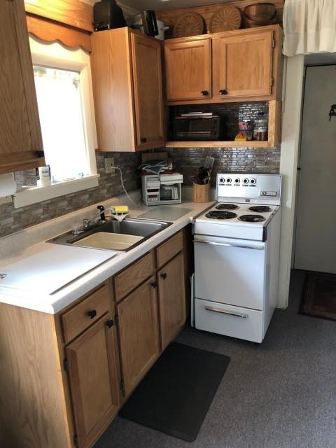 Kitchen features range, sink, full size refrigerator